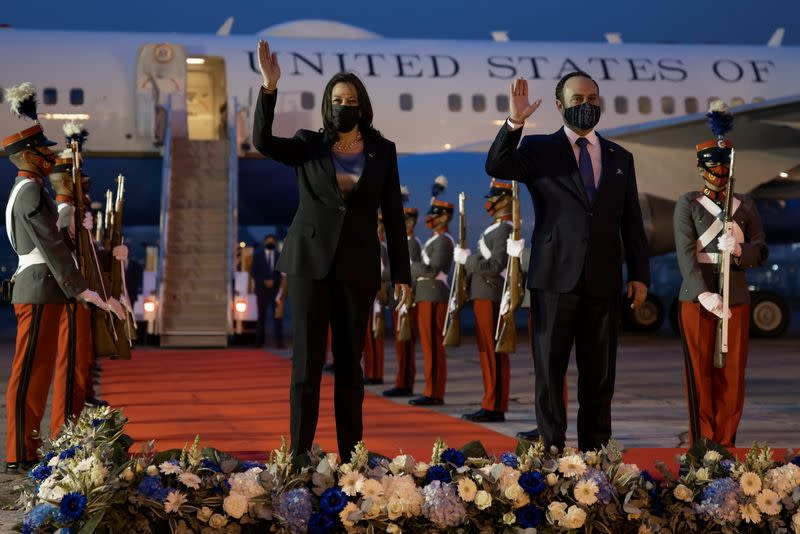 U.S. Vice President Kamala Harris and Guatamala's Foreign Minister Pedro Brolo wave upon her arrival at Guatemalan Air Force Central Command in Guatemala City