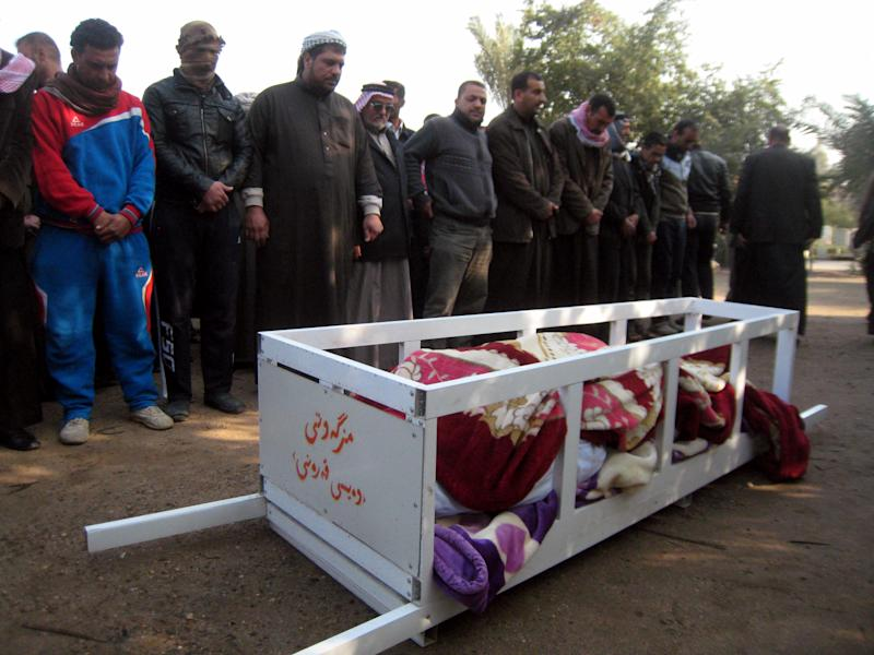 In this Thursday, Jan. 23, 2014 photo, mourners pray over the coffin of Haitham Abdo Rahman, 38, who was killed in a bombing, before his burial at the cemetery in Fallujah, Iraq. Islamic militants controlling a mainly Sunni area west of Baghdad are so well-armed that they could occupy the capital, members of Iraq's al-Qaida branch - known as the Islamic State of Iraq and the Levant - have taken over parts of Ramadi, the capital of the largely Sunni western province of Anbar. (AP Photo)