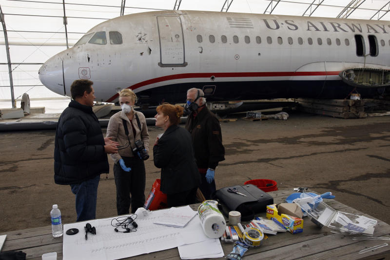 As they stand near the wreckage of US Airways flight 1549 Saturday, March 19, 2011, at a storage facility in Kearny, N.J., Stephen Ryan, left, talks with exhibit designer Eve Bartolo, second left, and her assistants Alois Osti, right, and Katherine Burdett as they prepare to move the airplane to an aviation museum in Charlotte, N.C. (AP Photo/Mel Evans)