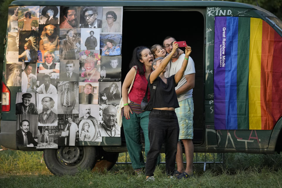 People strike a pose at Pride Park, a venue for artistic shows ahead the Pride 2021 in Bucharest, Romania, Friday, Aug. 13, 2021. The 20th anniversary of the abolishment of Article 200, which authorized prison sentences of up to five years for same-sex relations, was one cause for celebration during the gay pride parade and festival held in Romania's capital this month. People danced, waved rainbow flags and watched performances at Bucharest Pride 2021, an event that would have been unimaginable a generation earlier. (AP Photo/Vadim Ghirda)