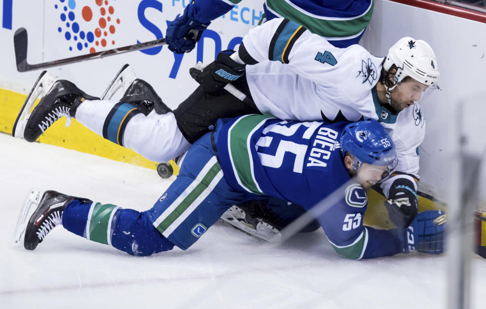 San Jose Sharks' Brenden Dillon (4) and Vancouver Canucks' Alex Biega (55) collide during the second period of an NHL hockey game in Vancouver, on Tuesday, April 2, 2019. (Darryl Dyck/The Canadian Press via AP)