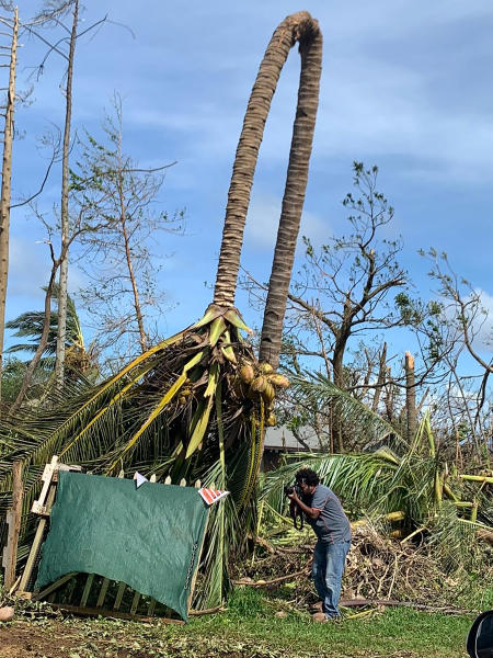 In this April 8, 2020, photo supplied by World Vision, a photographer takes photos of damage from Cyclone Harold on the island of Santo in Vanuatu. New Zealand announced Wednesday, April 8, 2020 it would help Vanuatu rebuild from the cyclone with aid of up to 500,000 New Zealand dollars ($300,000). Foreign Minister Winston Peters said Cyclone Harold had destroyed homes, infrastructure and crops.(World Vision via AP)