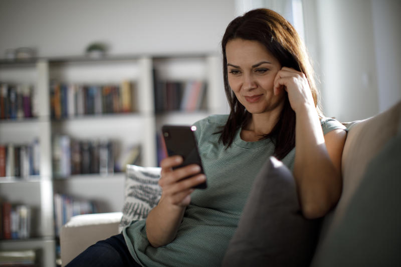 Smiling mature woman using mobile phone at home