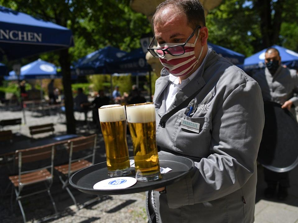 A waiter serves beer in the Park Cafe in Munich on May 18, 2020.