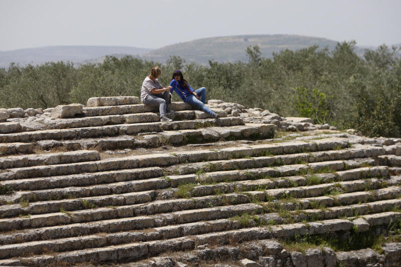 In this Saturday, April 6, 2013 photo, Italian tourists sit in the Roman Temple of Augustus in the village of Sebastia near the West Bank city of Nablus. The ancient town of Sebastia is one of the greatest archaeological sites of the Holy Land, attracting tourists and pilgrims over the centuries with its overlapping layers of history dating back 3,000 years. But visitors who come to the site today will find it in a state of neglect. (AP Photo/Majdi Mohammed)