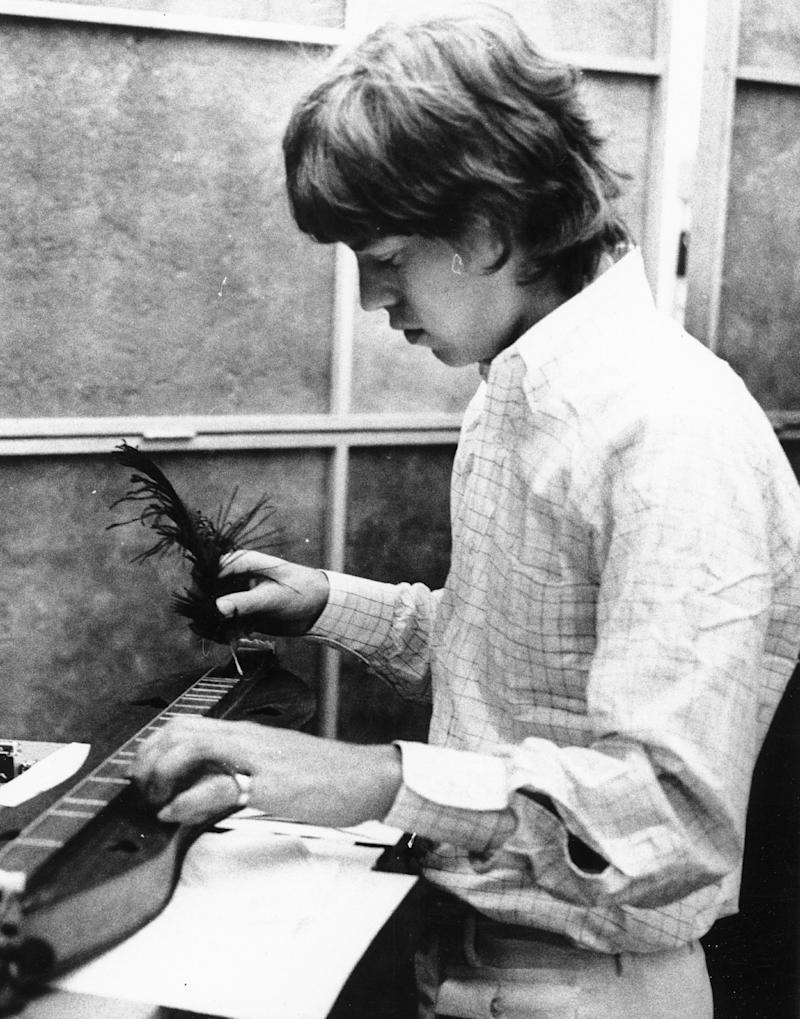 CIRCA 1965: Singer Mick Jagger of the rock and roll band 'The Rolling Stones' plucks out some notes using a feather quill on a dulcimer in a recording studio in circa 1965. (Photo by Michael Ochs Archives/Getty Images)