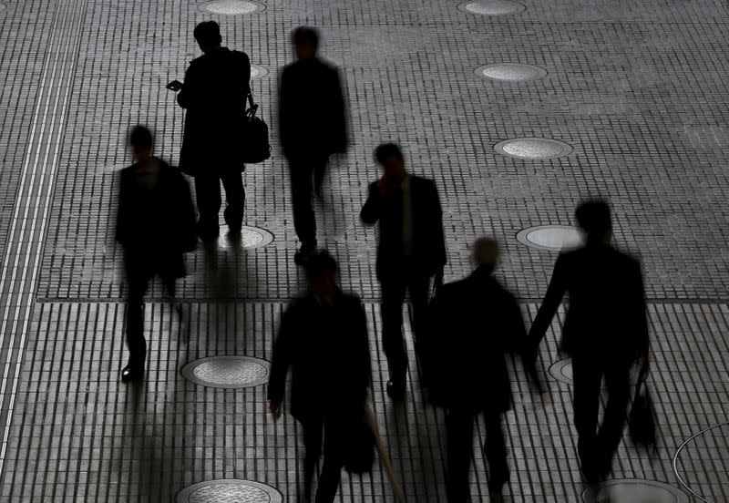 FILE PHOTO: People walk at an office building at a business district in Tokyo
