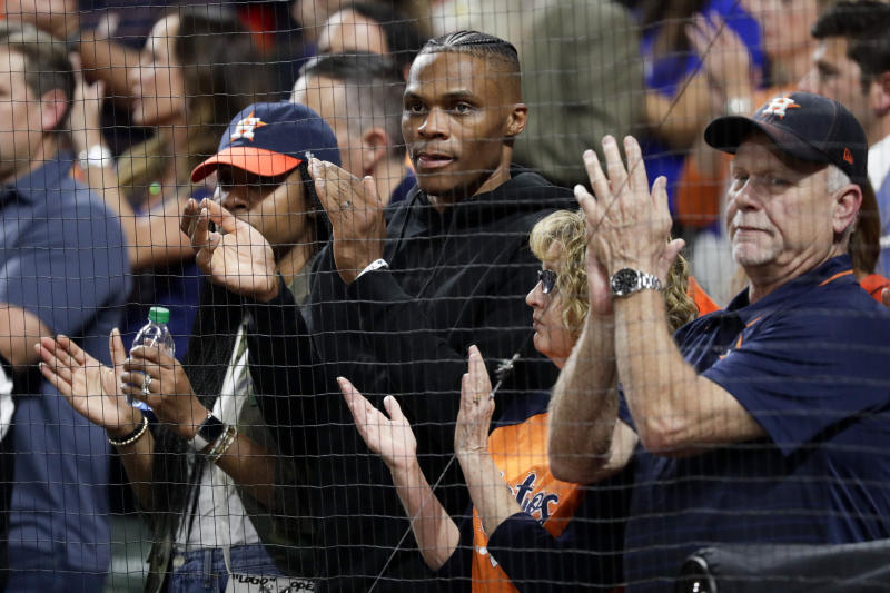 Houston Rockets's Russell Westbrook claps during the seventh inning in Game 2 of baseball's American League Championship Series between the Houston Astros and the New York Yankees Sunday, Oct. 13, 2019, in Houston. (AP Photo/Eric Gay)