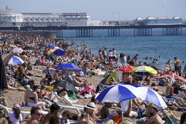 People enjoy the warm weather at Brighton beach in West Sussex. (Photo: Steve ParsonsPA)