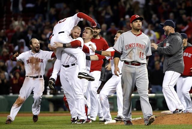 Boston Red Sox center fielder Grady Sizemore (38) jumps into the arms of teammate Jonny Gomes as he and teammates celebrate his walk-off single to defeat the Cincinnati Reds 4-3 in the 12th inning of a baseball game at Fenway Park in Boston, Tuesday, May 6, 2014. Reds first baseman Joey Votto (19) walks off the field. (AP Photo/Elise Amendola)