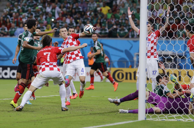 Croatian and Mexican players battle for the ball during the group A World Cup soccer match between Croatia and Mexico at the Arena Pernambuco in Recife, Brazil, Monday, June 23, 2014. (AP Photo/Sergei Grits)