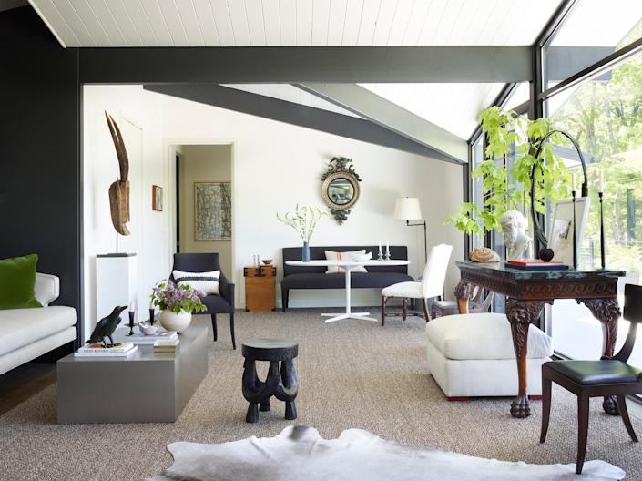 """<div class=""""caption""""> The main living space features multiple seating areas, including one for dining. The convex Regency mirror on the far wall and the 19th-century Irish console against the window are among the first pieces that Smyth selected for the house. """"Acting as my own client is difficult because I see a room five different ways and I have to choose just one,"""" says Smyth. """"In some ways, it's similar to designing a showhouse."""" </div>"""