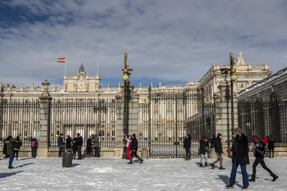 People walk in front of Royal Palace covered with snow in downtown Madrid, Spain, Sunday, Jan. 10, 2021. A large part of central Spain including the capital of Madrid are slowly clearing snow after the country's worst snowstorm in recent memory. (AP Photo/Manu Fernandez)