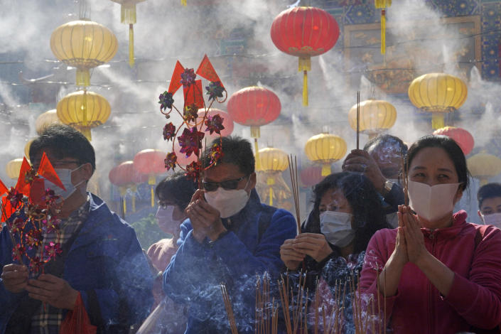 Worshippers wearing face masks to protect against the spread of the coronavirus, burn joss sticks as they pray at the Wong Tai Sin Temple, in Hong Kong, Friday, Feb. 12, 2021, to celebrate the Lunar New Year which marks the Year of the Ox in the Chinese zodiac. (AP Photo/Kin Cheung)
