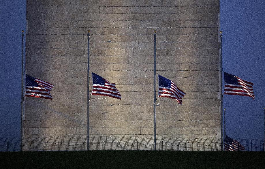 Flags around the Washington Monument in Washington fly at half-staff early Saturday, July 21, 2012, in tribute to the victims of the deadly mass shooting in Aurora, Colo. (AP Photo/J. David Ake)