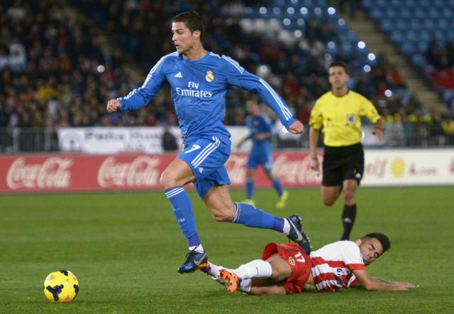 """Real Madrid's Cristiano Ronaldo (top) is challenged by Almeria's Jesus Joaquin Fernandez """"Suso"""" during their Spanish First Division soccer match at Juegos Mediterraneos stadium in Almeria November 23, 2013. REUTERS/Francisco Bonilla (SPAIN - Tags: SPORT SOCCER)"""