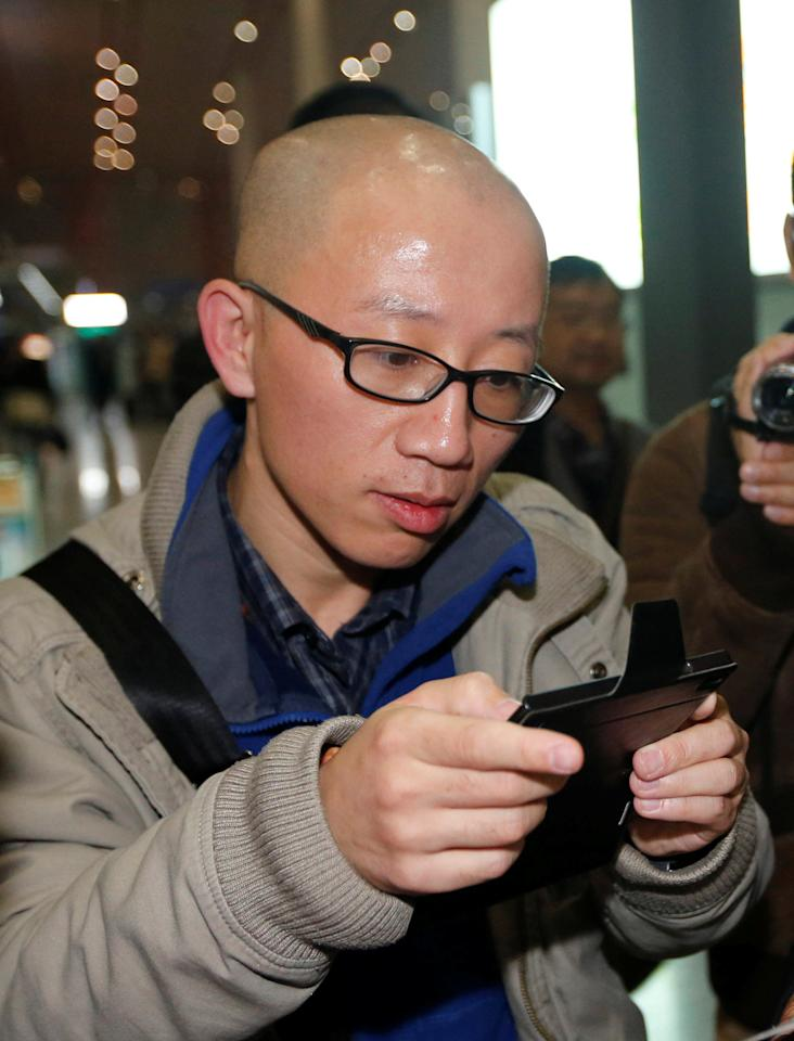 FILE PHOTO - Chinese dissident Hu Jia uses his mobile phone at Beijing airport November 6, 2013.  To match Insight CHINA-CONGRESS/RIGHTS  REUTERS/Kim Kyung-Hoon/File Photo