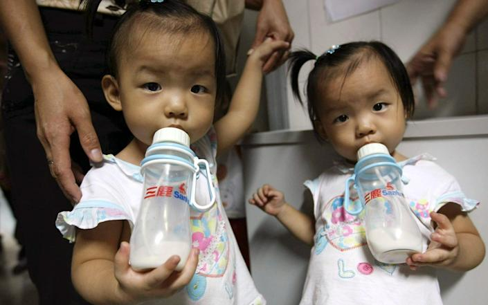 Two girls drink milk from a Sanlu brand bottle while waiting for a kidney stone test at a children's hospital in Shenzhen, Guangdong Province, southern China-Color China photo) / AP