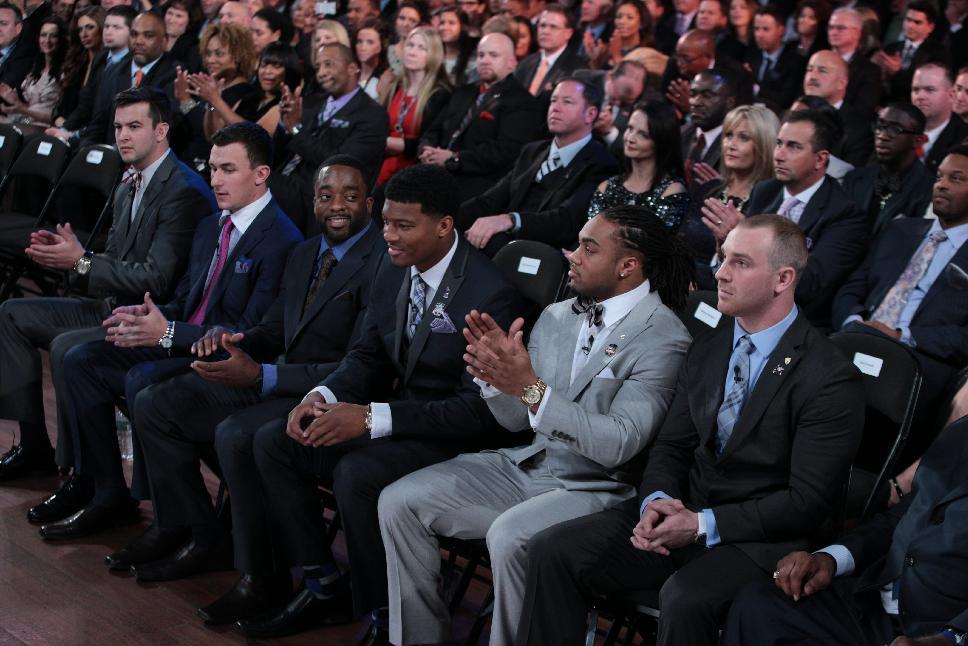 In this photo provided by the Heisman Trust, Heisman Trophy finalists, from left, Alabama quarterback AJ McCarron, Texas A&M quarterback Johnny Manziel, Boston College running back Andre Williams, Florida State quarterback Jameis Winston, Auburn running back Tre Mason and Northern Illinois quarterback Jordan Lynch react moments after it was announced that Winston is this year's trophy winner at the Best Buy Theater, Saturday, Dec. 14, 2013 in New York. (AP Photo/Kelly Kline, Heisman Trust)