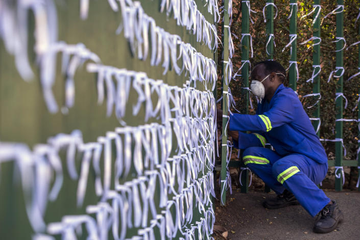 """FILE - In this July 29, 2020, file photo, Silva Cossa, the caretaker, ties ribbons onto the fence to represents a South African who has died from COVID-19, at St James Presbyterian church in Bedford Gardens, Johannesburg, South Africa. Africa's confirmed coronavirus cases have surpassed 1 million, but global health experts tell The Associated Press the true toll is several times higher. Whatever Africa's real coronavirus toll, the church has quietly been marking the country's """"known"""" number of deaths by tying white ribbons to its fence. The project's founders say each ribbon really stands for multiple people. (AP Photo/Themba Hadebe, File)"""