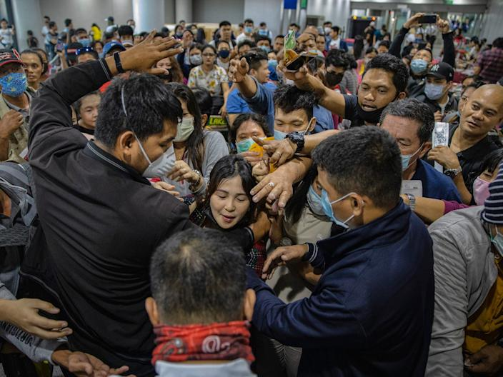 Airport security staff attempt to control the crowd as Filipinos hoping to get on flights out of Manila hours before it is placed on lockdown queue at Ninoy Aquino International Airport on March 14, 2020 in Manila, Philippines.