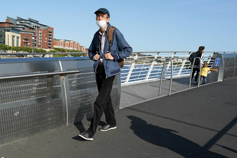 NEWCASTLE UPON TYNE, ENGLAND - SEPTEMBER 17: A man walks across the River Tyne on the Gateshead Millenium Bridge on September 17, 2020 in Newcastle upon Tyne, England. Almost two million people in north-east England will be banned from mixing with other households and pubs will close early as coronavirus cases rise. Health Secretary Matt Hancock announced the temporary restrictions will be in place from midnight due to concerning rates of infection. The measures affect seven council areas, Newcastle, Northumberland, North Tyneside, South Tyneside, Gateshead, County Durham and Sunderland. (Photo by Ian Forsyth/Getty Images)