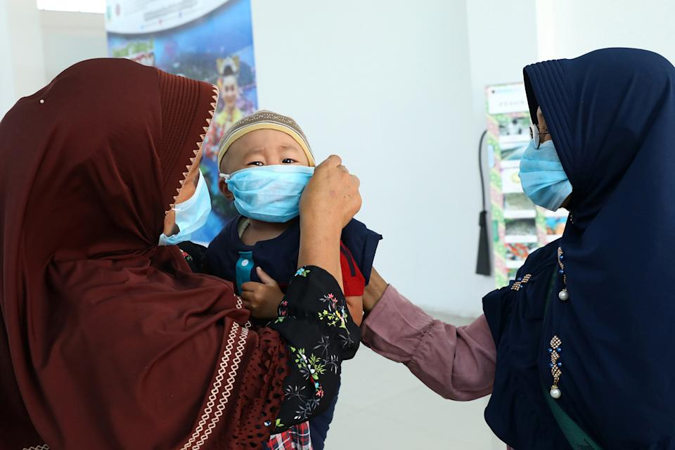 A toddler along with family members are seen wearing protective facemasks at the Raden Sadjad airport in Ranai, Indonesia's Natuna island, on February 3, 2020. - Returnees from Wuhan, mostly students, landed February 2 in the remote Indonesian island of Natuna and would be quarantined on the island for 14 days, as Natuna residents on February 3 protested at the government's decision to use it to quarantine evacuees from the Chinese city at the epicentre of the coronavirus outbreak. (Photo by RICKY PRAKOSO / AFP) (Photo by RICKY PRAKOSO/AFP via Getty Images)