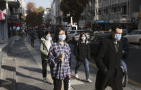 People wearing masks to help protect against the spread of coronavirus, walk, in Ankara, Turkey, Monday, Nov. 15, 2020. Turkish health ministry statistics show 93 people died Friday of COVID-19 amid a surge in infections, bringing the daily death toll to numbers last seen in April.(AP Photo/Burhan Ozbilici)