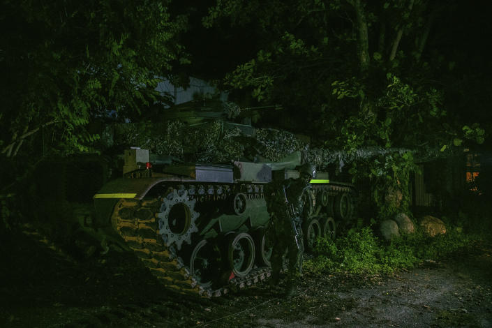In this photo released by the Military News Agency, a soldier and tank prepare for the annual Han Kuang live-fire drills in Hualian, eastern Taiwan in the early hours of Tuesday, Sept. 14, 2021. (Military News Agency via AP)