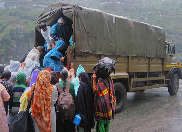 In this handout photograph received from the Indo-Tibetan Border Police (ITBP) on June 27, 2013, Indian flash flood evacuees board a truck as heavy rain falls at Govindghat in northern Uttarakhand state. Rescue workers stepped up the search for bodies June 27 in India's flood ravaged north, as mass cremations of victims already discovered got underway amid fears of outbreaks of disease , officials and reports said. AFP PHOTO / ITBP