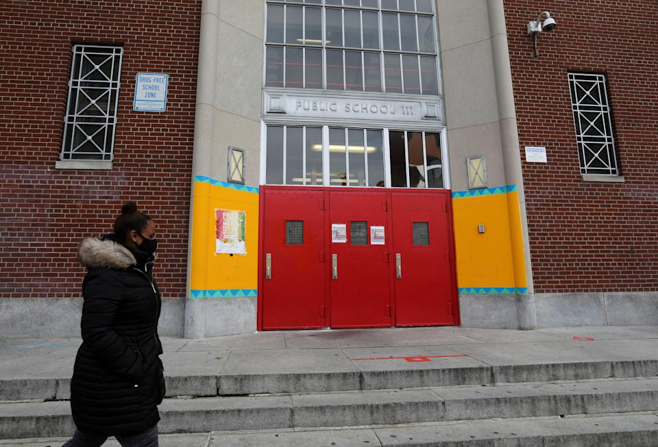 A woman goes away in front of the entrance to a public school in New York, USA on November 19, 2020.  (Wang Ying / Xinhua via Getty)