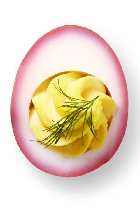 """<p>An egg that's pretty and tasty? No need to say more!</p><p>In a medium saucepan, heat 8 cups water, 4 medium beets, peeled and thinly sliced, 2 cups distilled white vinegar and 1 tablespoon salt to boiling on high. Reduce heat to simmering; cook 20 minutes. Cool liquid completely. Remove and reserve beets. Transfer pickling liquid to gallon-size resealable bag set in large bowl; add 12 peeled hard-cooked eggs. Squeeze air our of bag and seal, making sure eggs are submerged. Refrigerate 1 hour. Remove eggs from liquid and blot completely dry with paper towels before using.</p><p>To make the horseradish filling, mash yolks with 3 tablespoons mayo, 1/4 cup prepared horseradish, drained very well, 1 tablespoon Worcestershire sauce, and 1/2 teaspoon salt. Pipe into beet-dyed egg whites; garnish with fresh dill.</p><p><em><strong>Recipe courtesy of <a href=""""https://www.goodhousekeeping.com/food-recipes/easy/g606/deviled-eggs-recipes"""" rel=""""nofollow noopener"""" target=""""_blank"""" data-ylk=""""slk:Good Housekeeping"""" class=""""link rapid-noclick-resp"""">Good Housekeeping</a>. </strong></em></p>"""