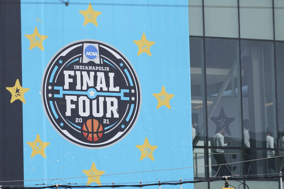 A basketball team walks through a crosswalk to the Indiana Convention Center for the NCAA college basketball tournament, Wednesday, March 17, 2021, in Indianapolis. (AP Photo/Darron Cummings)