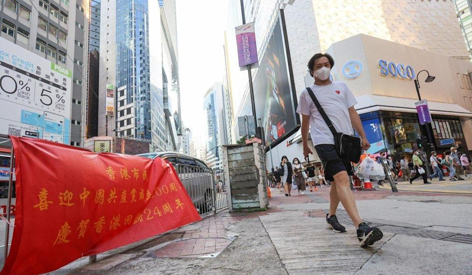 A Hong Kong resident walks past a banner celebrating the 24th anniversary of the city's return to Chinese sovereignty after one promoting the Falun Gong was removed. Photo: May Tse