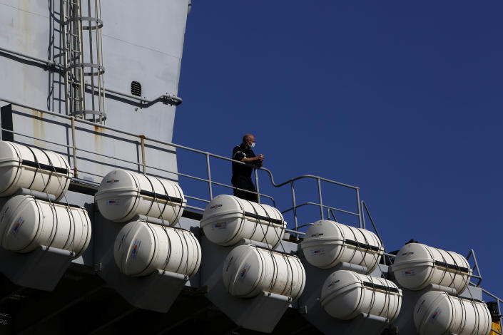 """A French crew member stands at France's nuclear-powered aircraft carrier Charles de Gaulle in Limassol port, Cyprus, Monday, May 10, 2021. With the Task Force's deployment on its mission named """"Clemenceau 21,"""" France is assisting in the fight against terrorism while projecting its military power in regions where it has vital interests. (AP Photo/Petros Karadjias)"""
