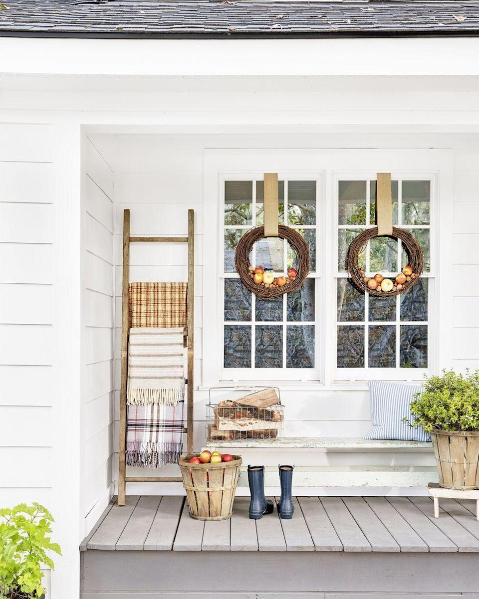 <p>Hang a pair grapevine wreaths adorned with apples on porch windows or a single wreath on the front door. For an extra fall touch, lean a rustic ladder up against the porch wall and drape warm fall blankets over the rungs. </p>