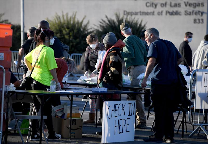 People arrive at a temporary homeless shelter set up in a parking lot at Cashman Center in Las Vegas.