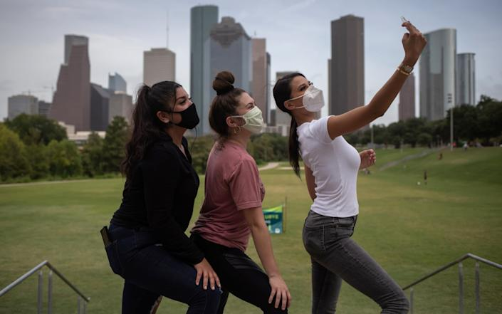 Houston residents Teresa Torres, Ilse Gonzalez and Vanessa Agudelo took time out for a selfie after making care packages for the local homeless community. The coronavirus outbreak in the US worsened on Tuesday with more states reporting record rises in new cases - REUTERS/Adrees Latif