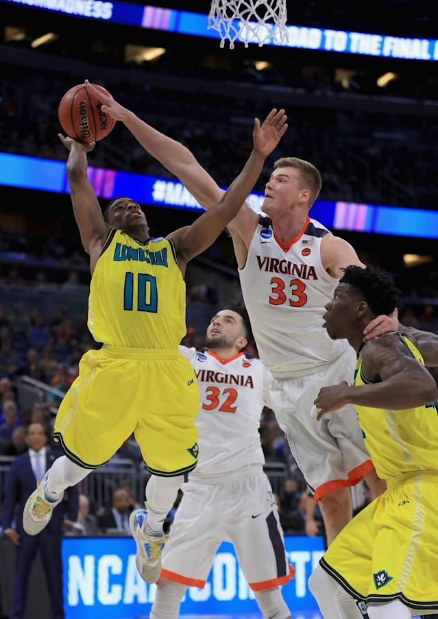 <p>Denzel Ingram #10 of the North Carolina-Wilmington Seahawks drives to the basket against Jack Salt #33 of the Virginia Cavaliers during the first round of the 2017 NCAA Men's Basketball Tournament at Amway Center on March 16, 2017 in Orlando, Florida. (Photo by Mike Ehrmann/Getty Images) </p>