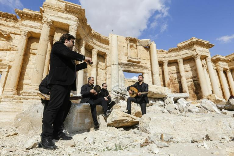 Syrian musicians play at the site of the damaged Roman amphitheatre in the ancient city of Palmyra, on March 4, 2017