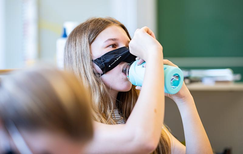 12 August 2020, North Rhine-Westphalia, Münster: A pupil of class 8a of the comprehensive school in Münster, lifts her mouth and nose mask to have a drink. The federal state of North Rhine-Westphalia is starting regular school operations again with compulsory masks after the summer holidays. Photo: Guido Kirchner/dpa (Photo by Guido Kirchner/picture alliance via Getty Images)