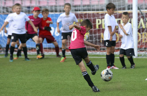 In this photo taken on Thursday, May 17, 2018, a boy shoots towards the goal, during a children soccer tournament at the Start Stadium in Saransk, Russia. The Start Stadium in Saransk may not look like much, but its the jumping-off point for hundreds of young Russians dreams of soccer stardom.(AP Photo)