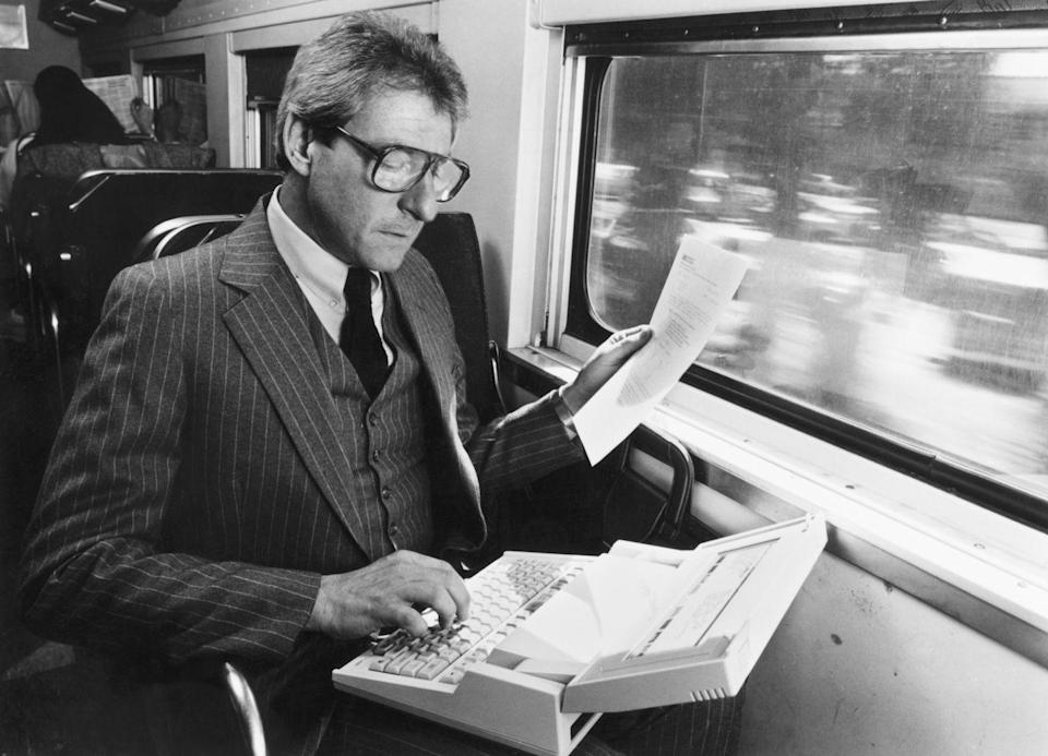 <p>A businessman uses a Hewlett-Packard laptop during his commute by train. HP's first laptop computer was an industry breakthrough, weighed 8.5 lbs, and cost nearly $3,000 - a hefty price tag for its time!</p>