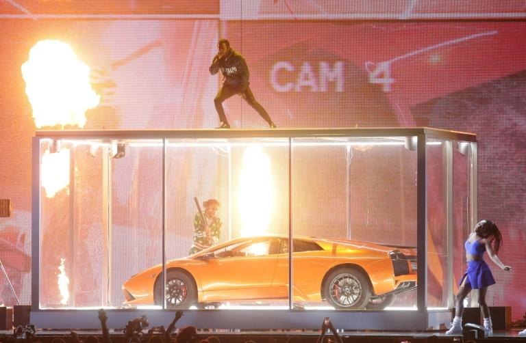 US rapper Kendrick Lamar performed live, standing on top of a huge box containing a sports car, which was smashed to pieces as the song went on