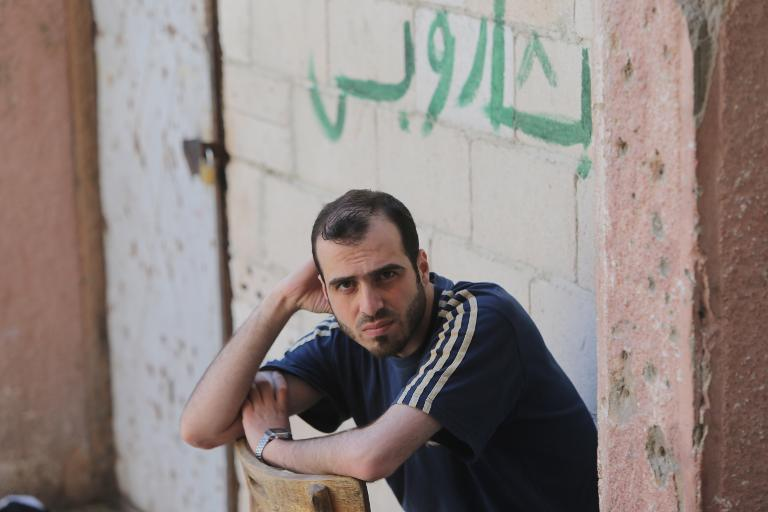 "A Syrian rebel fighter who surrendered to the government during the siege of Homs sits in front of graffiti reading in Arabic ""Bashar [al-Assad], nothing else"" at the Al-Andalous school turned into a detention center on May 13, 2014"