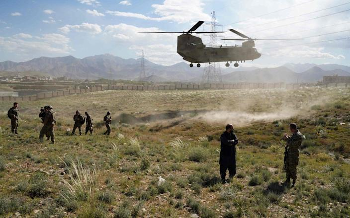 In this file photo taken on June 6, 2019, a US military Chinook helicopter lands on a field outside the governor's palace during a visit by the commander of US and NATO forces in Afghanistan, General Scott Miller, and Asadullah Khalid, acting minister of defense of Afghanistan, in Maidan Shar, capital of Wardak province.