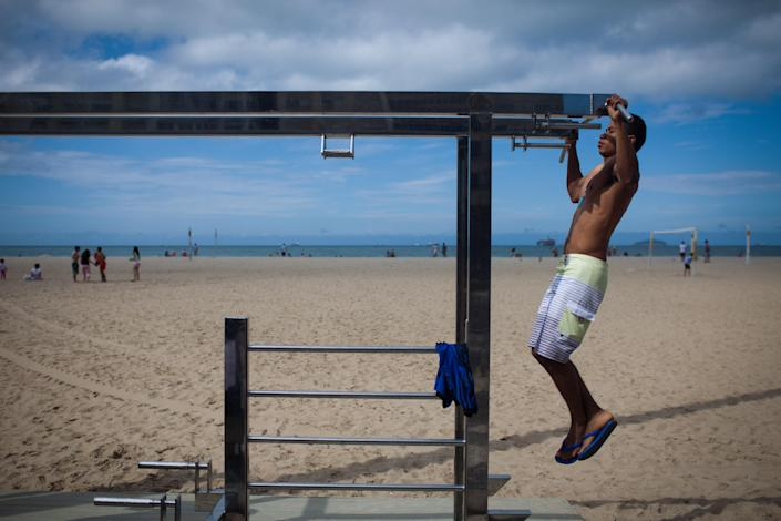 In this July 17, 2012 photo, a man wearing Havaianas sandals exercises on Copacabana beach in Rio de Janeiro, Brazil. In Brazil, literally everyone wears Havaianas, the now world-famous brand of rubber and plastic flip-flops that's celebrating its 50th birthday this year. (AP Photo/Felipe Dana)
