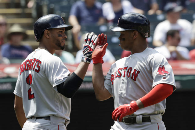 Boston Red Sox's Rafael Devers, right, is congratulated by Xander Bogaerts after Devers hit a solo home run in the third inning in a baseball game against the Cleveland Indians, Wednesday, Aug. 14, 2019, in Cleveland. (AP Photo/Tony Dejak)