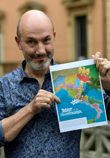 "French comics writer Jean-Yves Ferri shows off the future front page of the latest Asterix adventure, ""Asterix and the Race through Italy"" (showing the French edition title), to hit bookshelves in October"