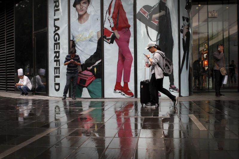 """People use smartphones outside the late designer Karl Lagerfeld's flagship store in Beijing, Thursday, June 6, 2019. China's Commerce Ministry says it will release a list of """"unreliable"""" foreign companies in the near future. The Chinese commerce ministry spokesman did not give a date Thursday during a weekly briefing. But he said the process of drawing up the list was underway. (AP Photo/Andy Wong)"""